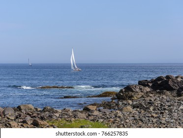 A sailboat makes it's way along the rocky shore line in Ogunquit
