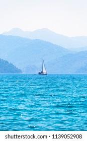 Sailboat in the Mediterranean on blue mountains background in Marmaris.  August 2017 Muğla-Turkey