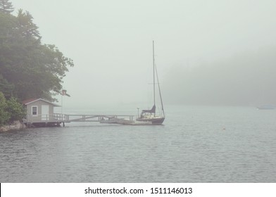 Sailboat moored at a dock on a very foggy day in Maine