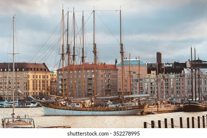 Sailboat moored in North Harbour in Helsinki, Finland. On waterfront there are houses built in different architectural styles in different historical periods.