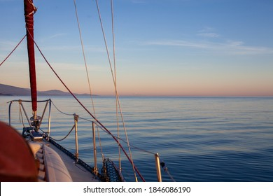 A sailboat motors at sunset along the coastline of British-Columbia's Sunshine Coast, along the Pacific Northwest on a calm day