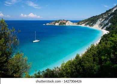 Sailboat near beach with light blue water on Gidaki on the Ithaca (Ithaki or Ithaka) island like paradise with blue sky in Greece Europe
