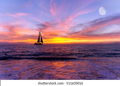 Sailboat ocean sunset is a silhouette of a sailboat sailing along the ocean water with a colorful vivid sunset sky and the moon rising in the sky.