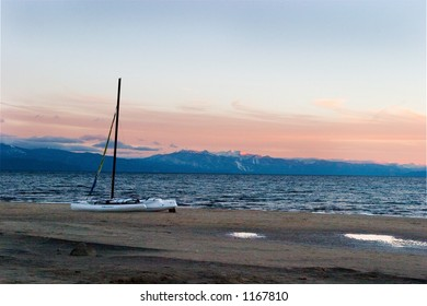 Sailboat on beach at sunset