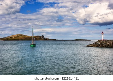 Sailboat on Dublin Bay, with Irelands Eye in the background, near the seaport village of Howth.