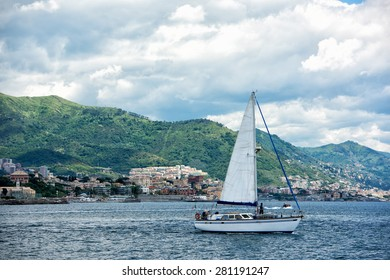 sailboat on genoa town cityscape panorama from the sea on cloudy day