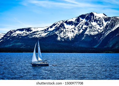 Sailboat on Lake Tahoe as the snow melts from the mountaintops in spring.
