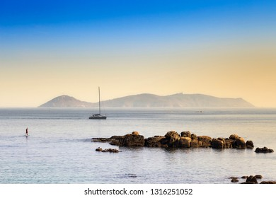 Sailboat and Ons Island national park in foggy sunset