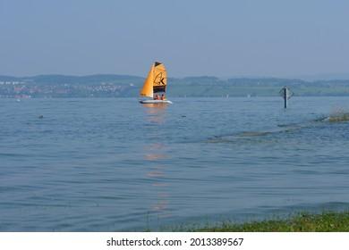 sailboat with orange sail near harbor Altnau. German shore at horizon. lake Bodensee, CH Switzerland. 20th July 2021