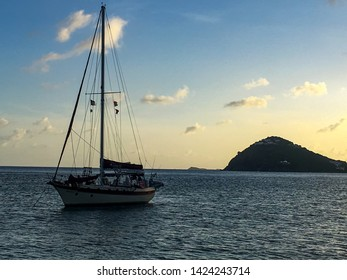 A sailboat outlined by the beautiful light of a Caribbean sunset.