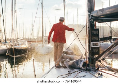 Sailboat owner or yachtsman uses hose to wash of salt water from yachr deck when docked or parked in marina on sunset, after long day of sailing race or competition