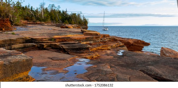 Sailboat parked along the rocky shoreline of the Devils Island in the Apostle Islands