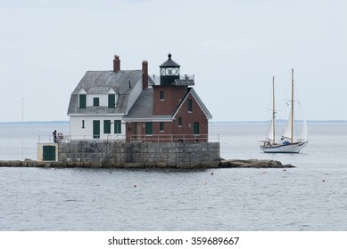 Sailboat passes by Rockland Breakwater lighthouse, which lies at the end of a long breakwater, during high tide in Rockland Harbor, in mid coast Maine. It is a favorite tourist attraction.