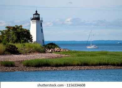 Sailboat passing by tower of Black Rock Harbor lighthouse, also referred to as Fayerweather Island light, near the rocky shoreline of Seaside Park, on a warm summer day in Bridgeport, Connecticut.