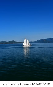 A sailboat plies the waters of the Salish Sea near the San Juan Islands in Washington State