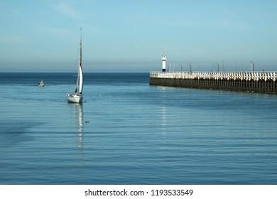 Sailboat in the port entrance of Nieuwpoort , Belgium