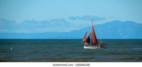 Sailboat with red sail in the Santa Barbara channel on the gold coast of California United States