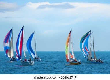 Sailboat regatta race with colorful spinnaker sails up on a beautiful sunny morning.
