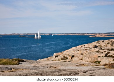 Sailboat and rocky coastline in sea archipelago