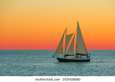 Sailboat or Sail yacht. Private cruise or sunset tour. Summer vacations on ocean or Gulf of Mexico Florida. Yachting sport. Beautiful seascape. Red sky after sunset.