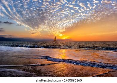 A Sailboat is sailing Along the Ocean at Sunset