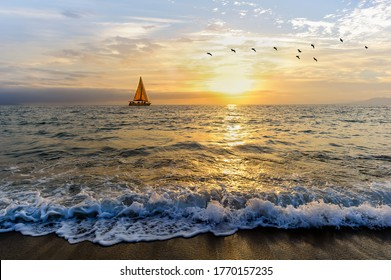 A Sailboat is Sailing Along the Ocean as a Vivid Colorful Sunset is in the Background and Birds Flying