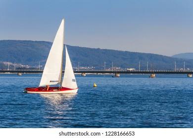 Sailboat sailing with Arousa island bridge at background
