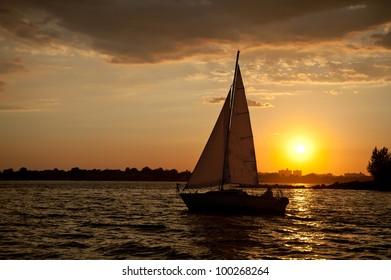 Sailboat sailing in calm waters again setting sun.