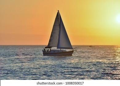 Sailboat sailing into the sunset.