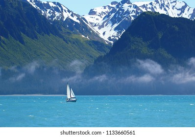 Sailboat sailing in misty weather in icy and cold waters of Whittier, Alaska