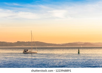 Sailboat sailing near maritime signaling buoy in Pontevedra bay at the evening