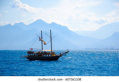 The sailboat is sailing in the sea with high mountain range and city as a background