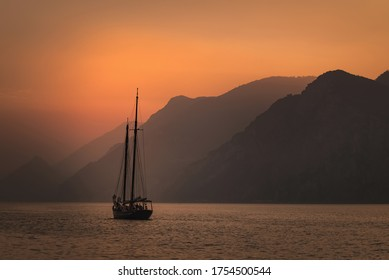 Sailboat sailing at sunset on the background of a mountain range. Traveling concept