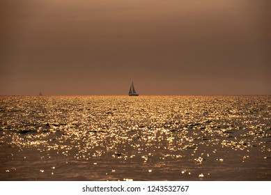 Sailboat sails on ocean in strange golden glow caused by sun shining through smoky skies created by smoke from nearby wild fire