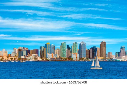A sailboat sails past the dramatic skyline of downtown San Diego, California. Other small boats are moored in the San Diego harbor. The San Diego Bay leads right into the Pacific Ocean.