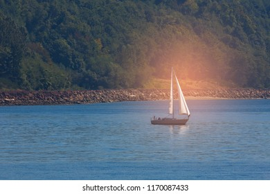 Sailboat in the sea in the evening sunlight over beautiful big mountains background, luxury summer adventure, active vacation in Mediterranean sea.