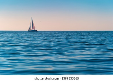 Sailboat in the sea in the evening sunlight over sky background. Luxury summer adventure or active vacation concept. Copy space.
