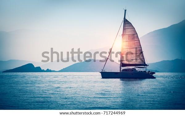 Парусная лодка в море в вечернем солнечном свете над красивыми большими горами фоне, роскошные летние приключения, активный отдых в Средиземном море, Турция