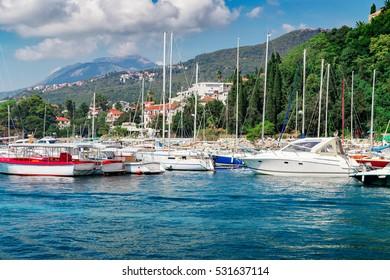Sailboat ships at marina near old town and high mountain