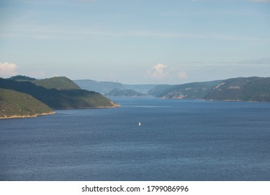 A sailboat is shown on the Saguenay Fjord in the Saguenay region of Quebec Canada