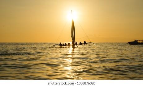 Sailboat With Sitting Tourists on Golden Sunset Sea - Boracay Island, Panay - Philippines