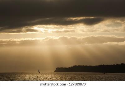 Sailboat Sunrise. Light rays shine down on an island near the historic town of Port Townsend, Washington, USA