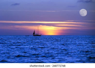Sailboat sunset moves across the ocean on it's journey lighted by the moon light and the setting sun.