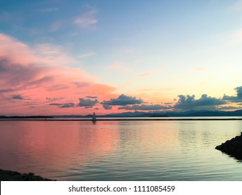 A sailboat at sunset on Lake Champlain in Burlington, Vermont. The vibrant pink sky transitions to a cool blue in both the sky and the water.