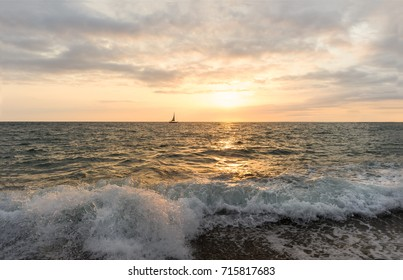 Sailboat sunset is a sailboat sailing along the ocean at sunset with a wave crashing to the shore.