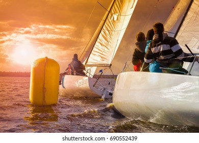 Sailboat at sunset. Sailing yacht race, regatta. Recreational Water Sports, Extreme Sport Action. Healthy Active Lifestyle. Summer Fun Adventure. Hobby