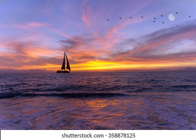 Sailboat sunset silhouette is a colorful vibrant orange and yellow cloudscape s