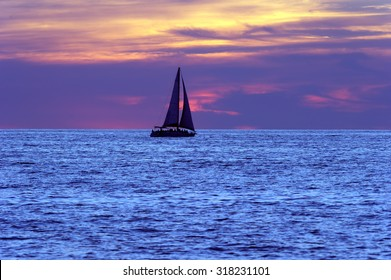 Sailboat sunset is a silhouetted boat and people moving along a blue sea with a colorful cloud filled sky in the background.
