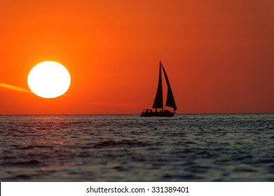 Sailboat Sunset is sailboat silhouetted a bright red sky with a bright white burning sun setting in the background.