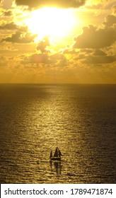 Barco de vela al atardecer con sol y nubes en la costa de Gipuzkoa, Euskadi